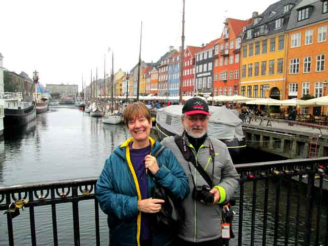 An old codger and his much-younger looking wife strike a touristic pose in Nyhavn.