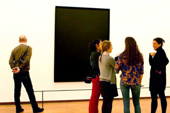 An art teacher tries to explain to her bemused students the meaning of one of Ad Reinhardt's black paintings.