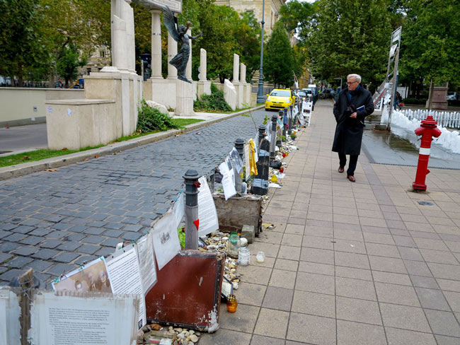 A pedestrian examens the personal effects and documents that make up the Living Memorial.